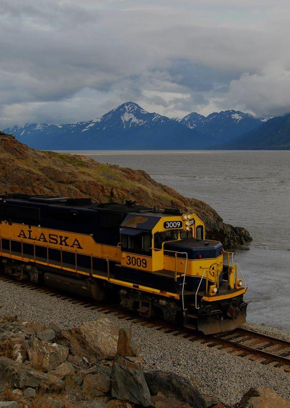 A train travels along a rocky shoreline with mountains in the distance