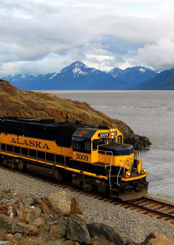 Alaska Railroad train travels past a large body of water