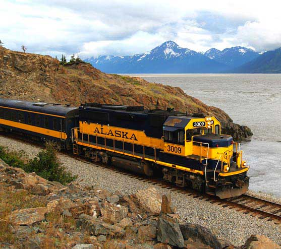 A train travels alongside a rocky shoreline