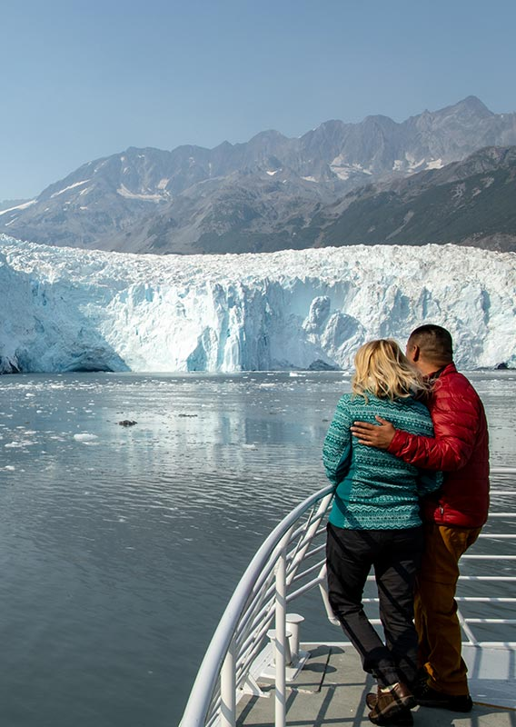 Two people stand at the railing of a boat, looking towards a glacier.