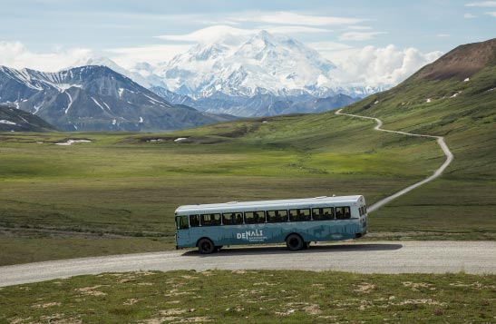A bus drives down a remote road in sparsely treed terrain and snow covered mountains in the distance