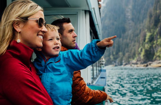 A family stands on a boat deck. A child points off into the distance.