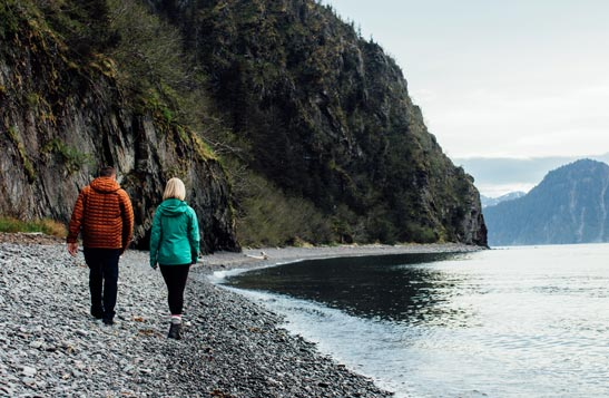Two people walk along a rocky beach below a lush cliffside.