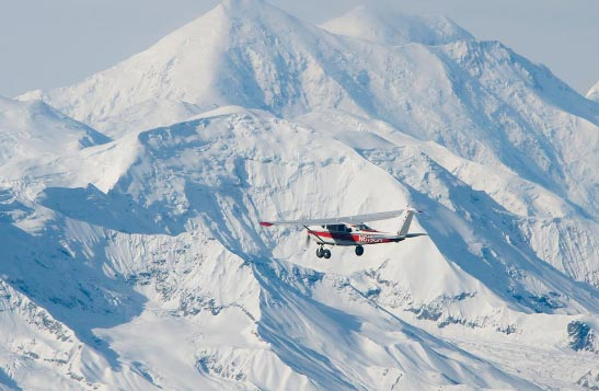 A propeller plane flies past snow-covered peaks