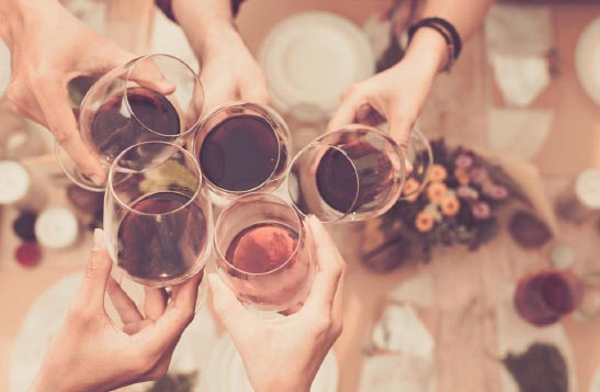 Five wine glasses join together in cheers
