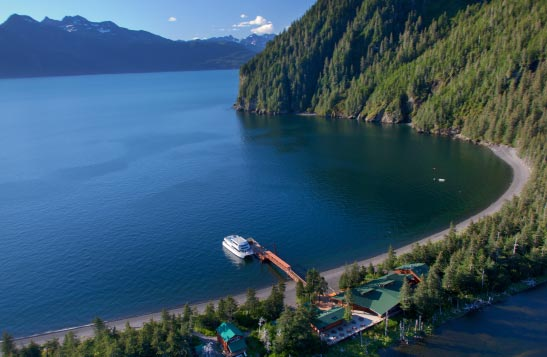 A boat is docked at the secluded Kenai Fjords Wilderness Lodge around steep forested hills
