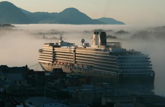 A cruise ship docked around foggy ocean