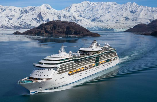A cruise ship moves past icy mountains and glaciers