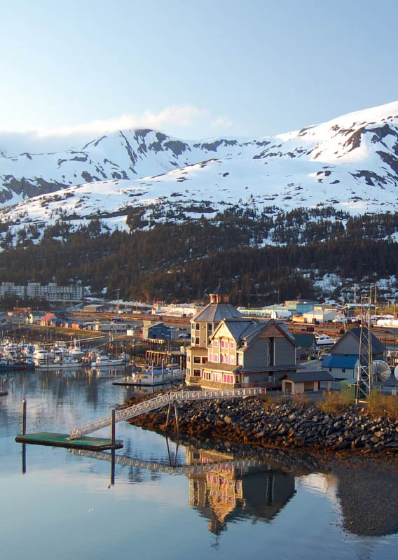 The harbor at Whittier with boats and snow-covered mountains behind the town.